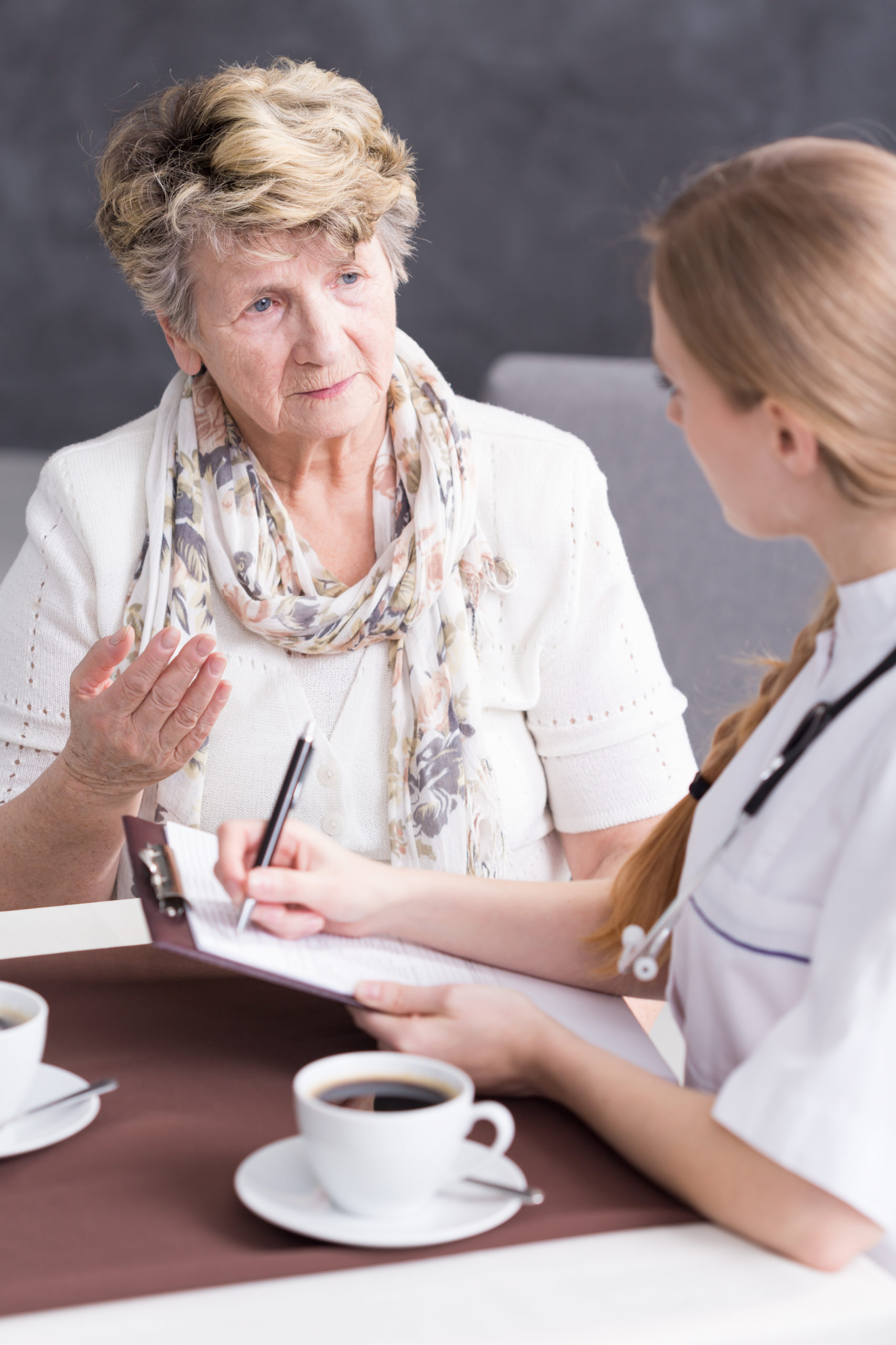 Senior talking with nurse about her ailments during home visit